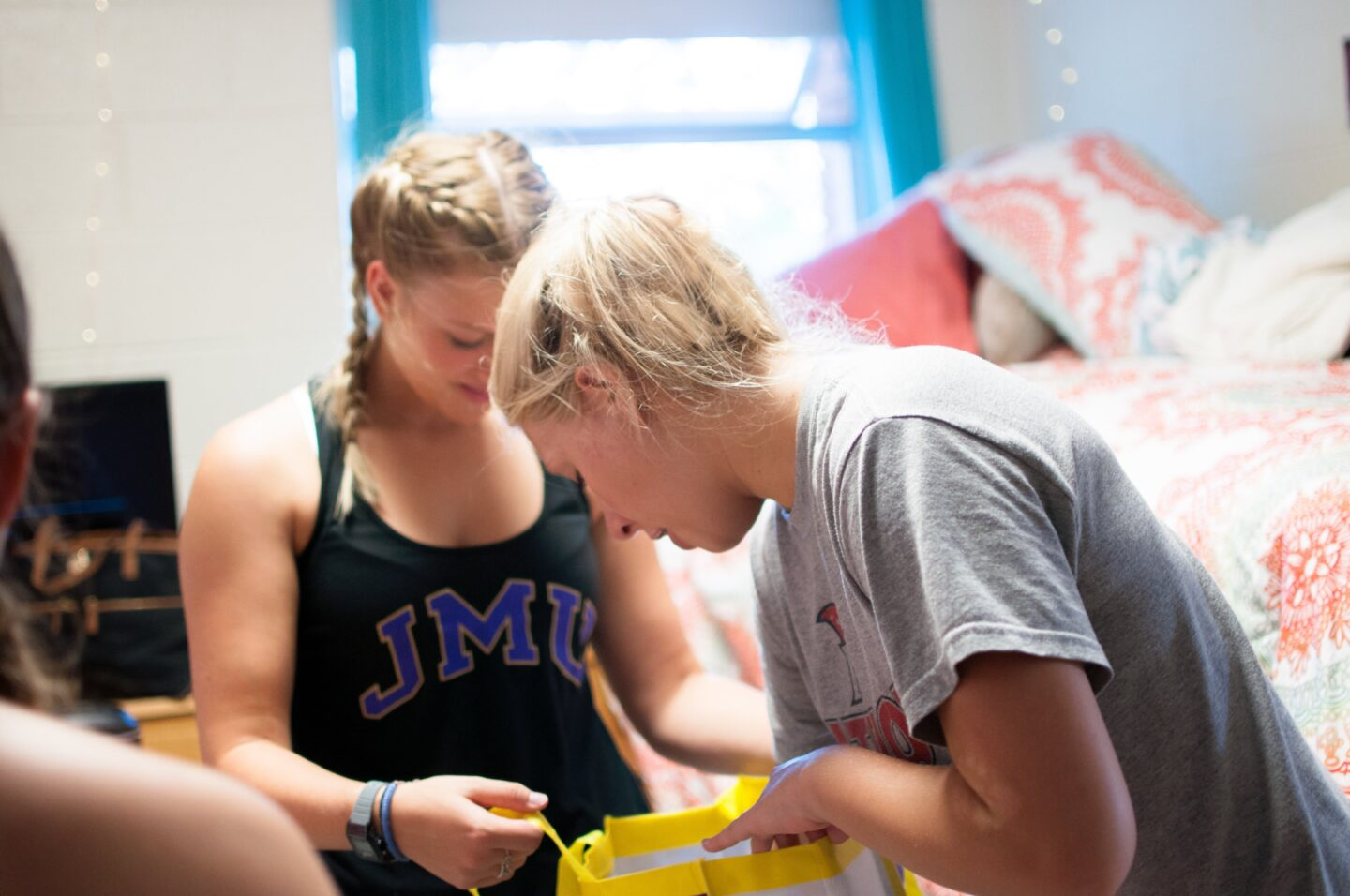 Two roommates in a college dorm organizing their bedroom and getting along