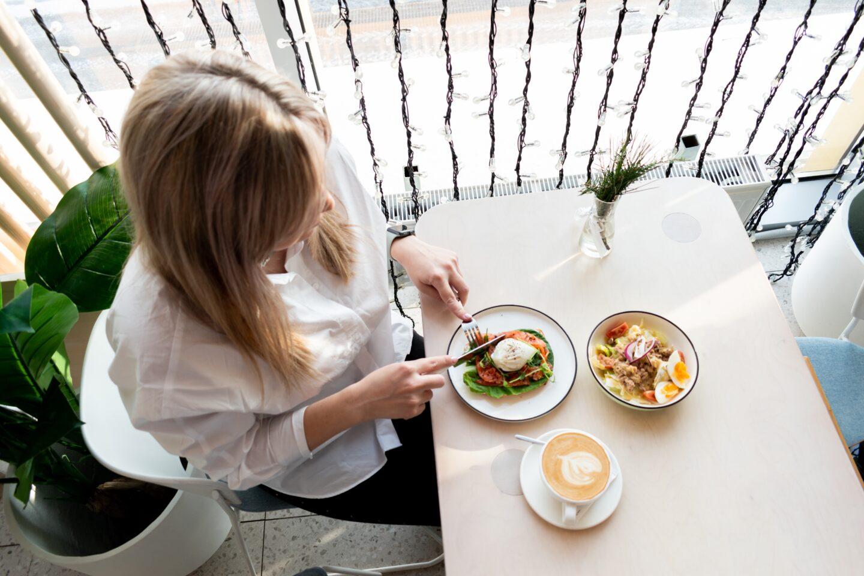 Girl eating lunch sitting near a window