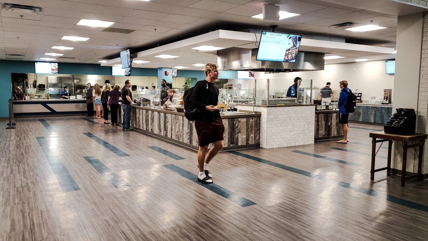 A dining hall at a college campus with students picking food